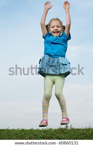 little girl jump om grass under sky - stock photo