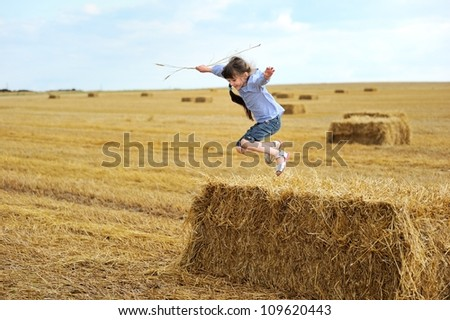 Little girl jumping from a top of haystack in the middle of the field - stock photo