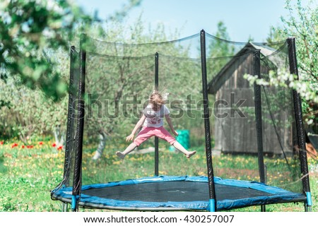 Little girl jumping on the trampoline outside in the summer - stock photo