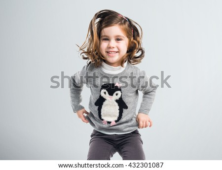 Little girl jumping over grey background - stock photo