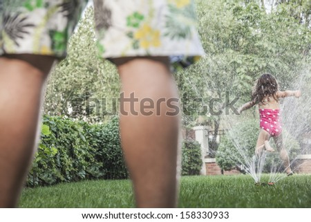 Little girl jumping through a sprinkle as father watched - stock photo