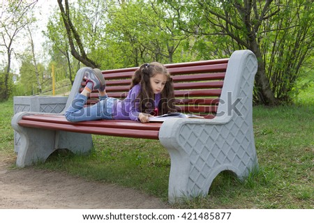 Little girl kid with beautiful long hair reading a book lying on a bench in spring park - stock photo