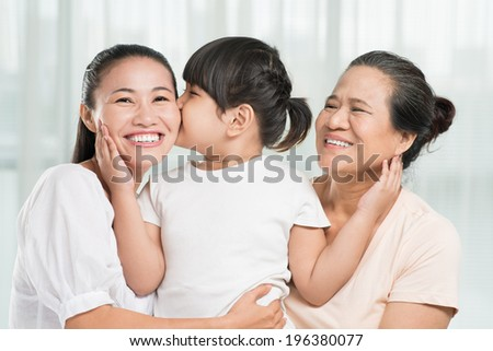 Little girl kissing her mother and bonding her granny - stock photo