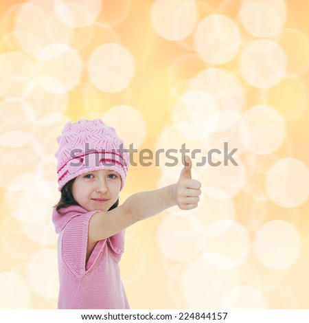 Little girl knitted hats showing thumb up.Happiness, winter holidays, new year, and childhood. - stock photo