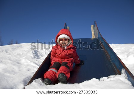 little girl laughing with happiness after a trip down the slide - stock photo