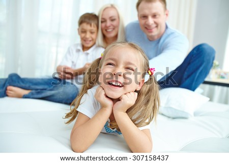 Little girl laughing with her family in the background - stock photo