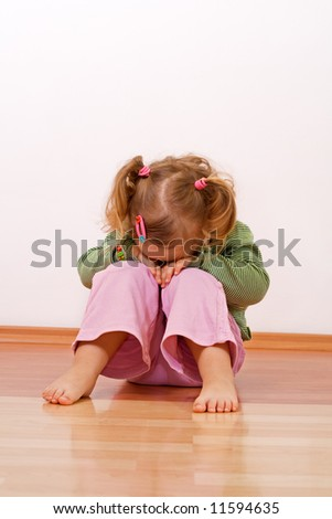 Little girl laying head on her knees - stock photo