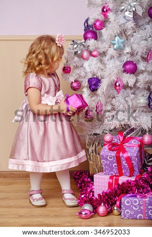 Little girl lays out the gifts under the Christmas tree. New Year. Holiday and fun. Merry Christmas. - stock photo