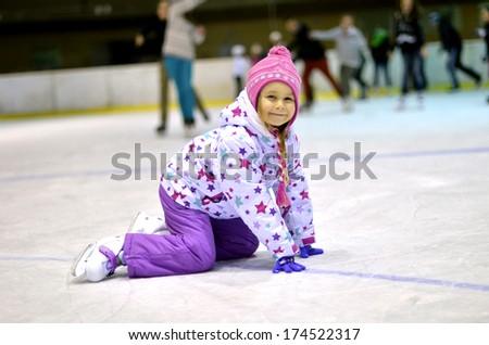 little girl learning ice skating - stock photo