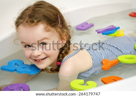 Little girl learning letters in the bath - stock photo