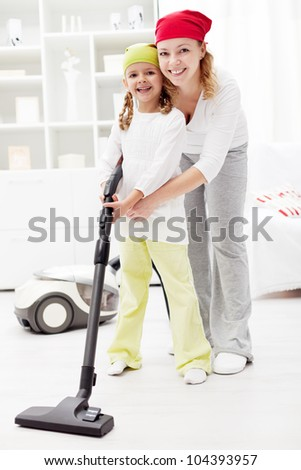 Little girl learning the household - vacuum cleaning together with mother - stock photo