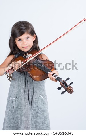 Little girl learning to play violin on white background isolated - stock photo