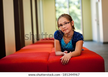 Little girl lifestyle shot in  a sunny room with her hands folded laying on a red couch with an out of focus background and  room for copy - stock photo