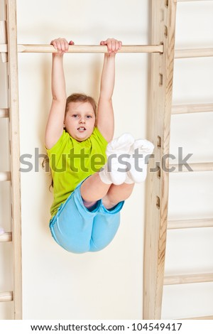 Little girl lifting legs on the wall bars - stock photo