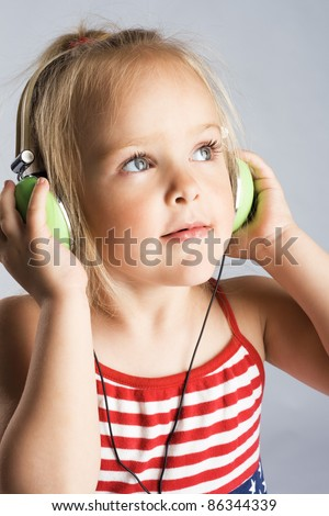 Little girl listening a music in earphones - stock photo