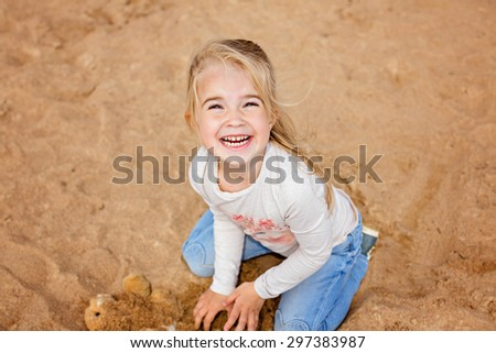 Little girl little girl sitting on the sand on the beach and grins, playing with the sand in the summer - stock photo
