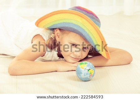 little girl looking at a small globe at home - stock photo