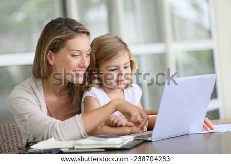 Little girl looking at laptop computer with her mom - stock photo