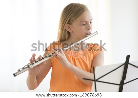 Little girl looking at sheet music while practicing flute at home - stock photo