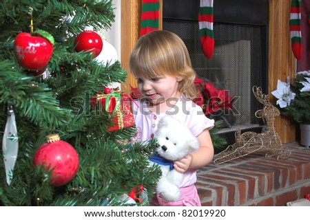 Little girl looking at the ornaments on christmas tree - stock photo