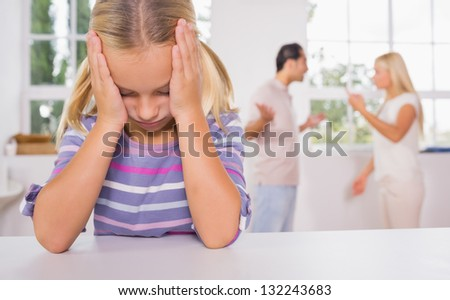 Little girl looking depressed in front of fighting parents in the kitchen - stock photo