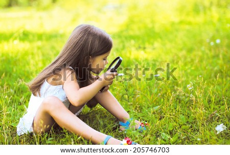 Little girl looking through a magnifying glass on flower - stock photo