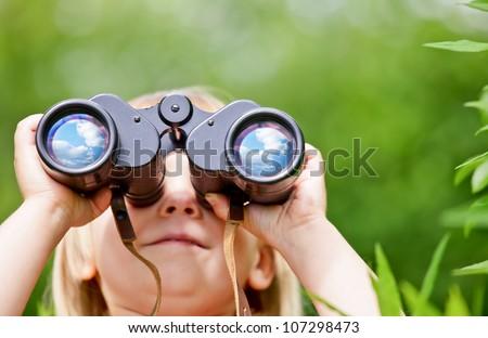 Little girl looking through binoculars outdoors - stock photo
