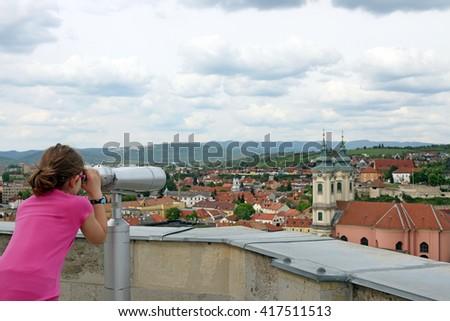 little girl looking through sightseeing binoculars on old town Eger Hungary - stock photo