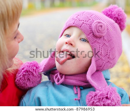 Little girl looking to her mother and making face - stock photo
