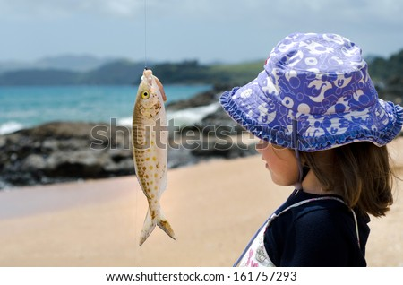 Little girl looks at a fish on a hook during casting fishing at sea from the beach - stock photo