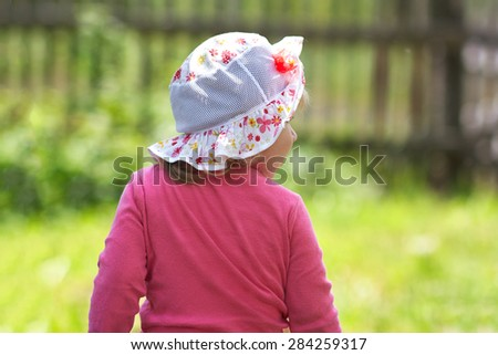 little girl looks back at the park - stock photo
