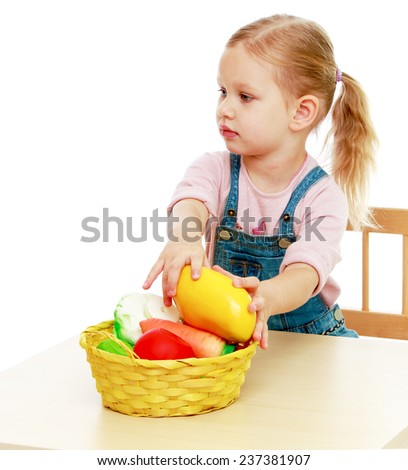 Little girl lying disassembled in a fruit basket.Childhood education development in the Montessori school concept. Isolated on white background. - stock photo