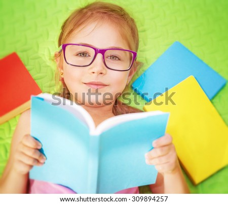 Little girl lying down on the floor at home and with pleasure reading book, wearing glasses, doing homework, back to school - stock photo