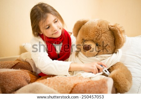 Little girl lying in bed and measuring teddy bears temperature with thermometer - stock photo