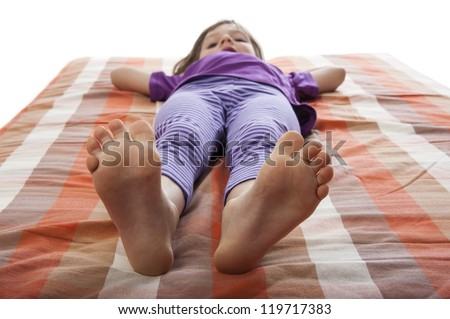 little girl lying on a bed - barefoot - stock photo