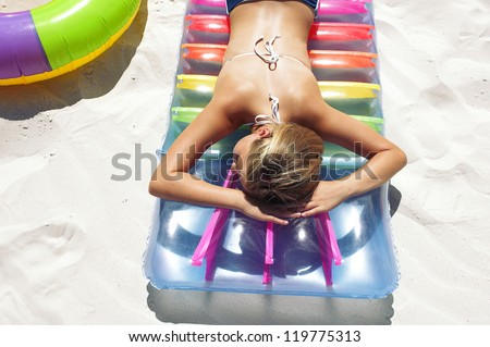 Little girl lying on air mattress on sandy beach and enjoys in sunbathing - stock photo