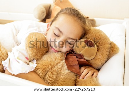 Little girl lying on bed with big brown teddy bear - stock photo