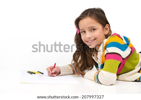 little girl lying on floor and smiling. side view of schoolgirl drawing picture - stock photo