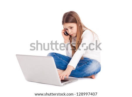 Little girl lying on floor working with a laptop and mobile phone - stock photo