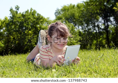 little girl lying on grass and play with tablet pc - stock photo