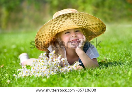 Little girl lying on the lawn - stock photo