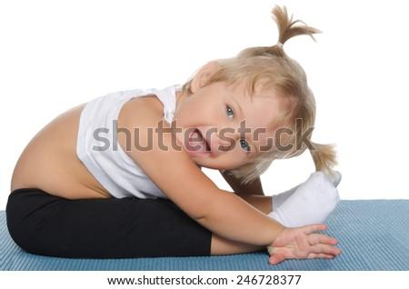 Little girl makes the slopes on blue mat - stock photo
