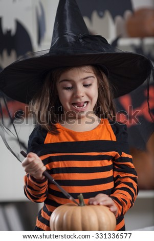 Little girl making face while trying to cut pumpkin - stock photo