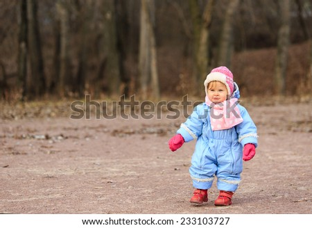 little girl making first steps in autumn park - stock photo