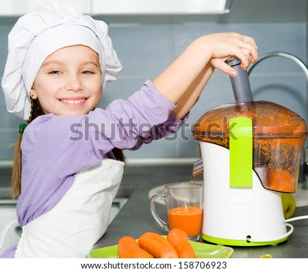 little girl making fresh carrot juice - stock photo
