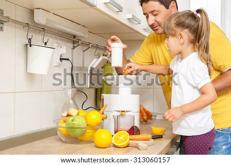 Little girl making fresh organic juice with her father assisting him in the kitchen - stock photo