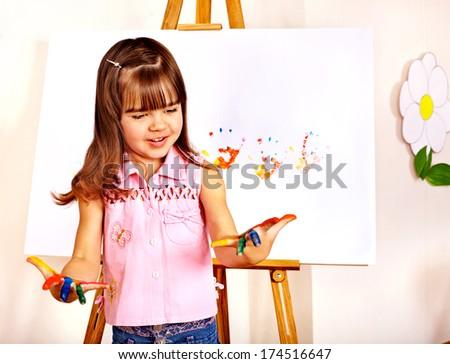 Little girl  making hand prints. - stock photo