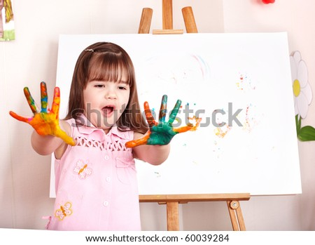 Little girl making handprints with paint. - stock photo