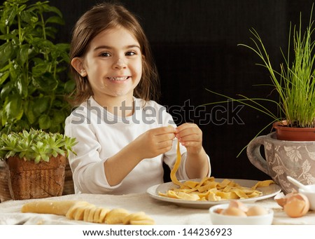 Little girl making pasta - stock photo