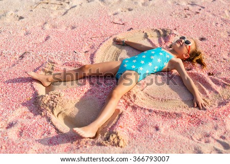 Little girl making sand angel on beautiful pink sand beach at tropical island of Barbuda in Caribbean - stock photo